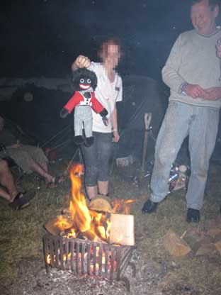 News Shopper: A 12-year-old girl danges the gollywog over the fire while BNP member John Coombes laughs