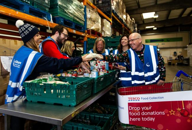 FareShare Chief Executive Lindsay Boswell (right), Emma Revie, Chief Executive of the Trussell Trust and Tesco Director Christine Heffernan with Tesco volunteers during the launch of the Tesco Food Collection at the FareShare regional Centre in Deptford,