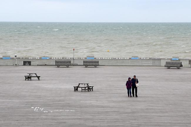 People walk along the pier in Hastings, East Sussex