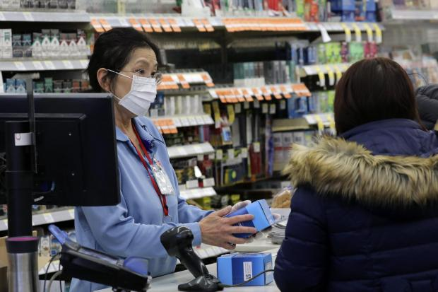 News Shopper: A sales clerk at a pharmacy rings up a purchase of face masks as fears of the coronavirus continue