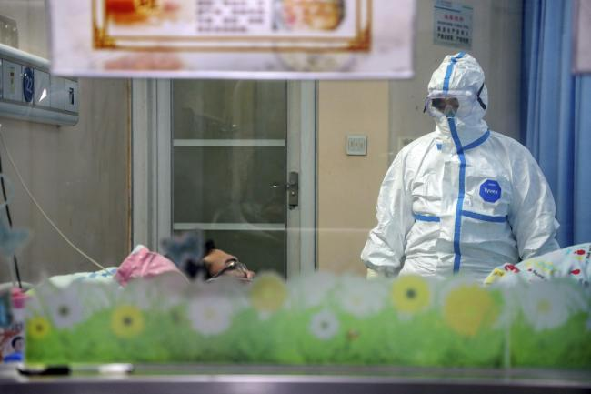 A doctor attends to a patient in an isolation ward at a hospital in Wuhan in central China's Hubei Province, Thursday, Jan. 30, 2020. (Chinatopix via AP)