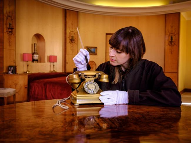 English Heritage Collections Curator Dr Olivia Fryman gives a recently donated 1930s gold telephone a final brush up before it goes on public display for the first time at Eltham Palace in London tomorrow.