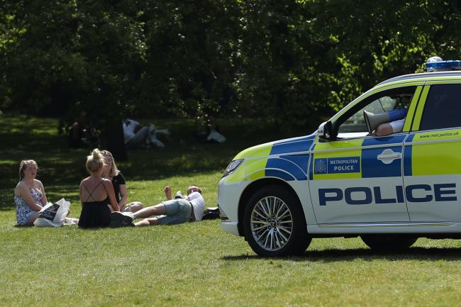 Police officers in a patrol car move sunbathers on in Greenwich Park, London