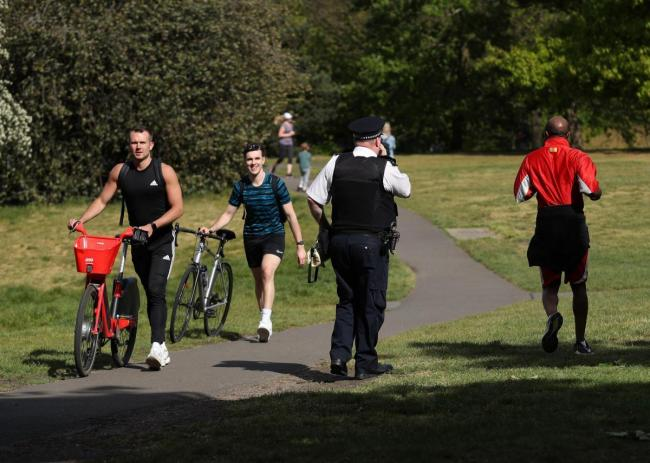 A police officer with a megaphone instructs people to keep moving in Greenwich Park earlier this month. Image: Yui Mok/PA Wire