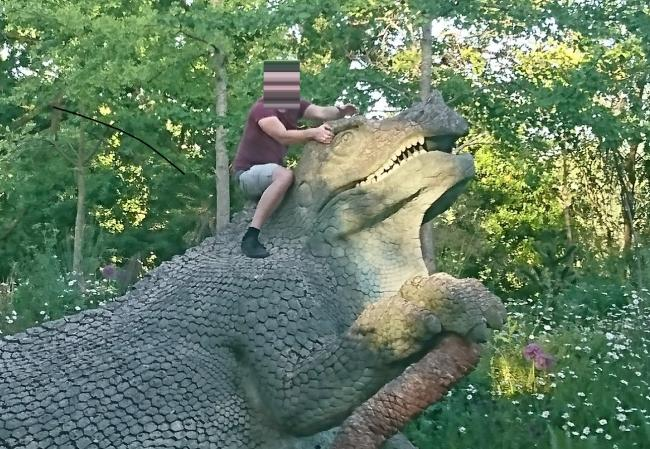 An image captured by a Crystal Palace resident on Thursday shows two men climbing the heritage-listed dinosaurs, while another takes photos.