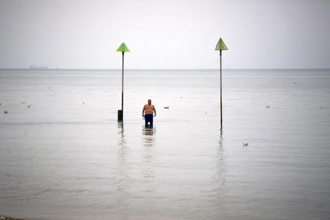 A man stands alone in the sea as the hot weather in Southend, Essex continues. Image: Victoria Jones/PA Wire