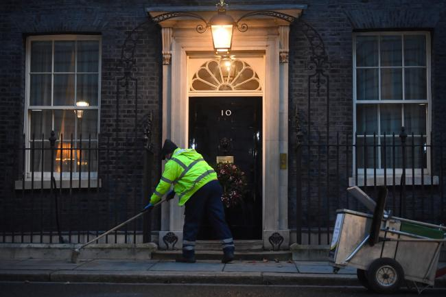 A man cleans the street in front of 10 Downing Street