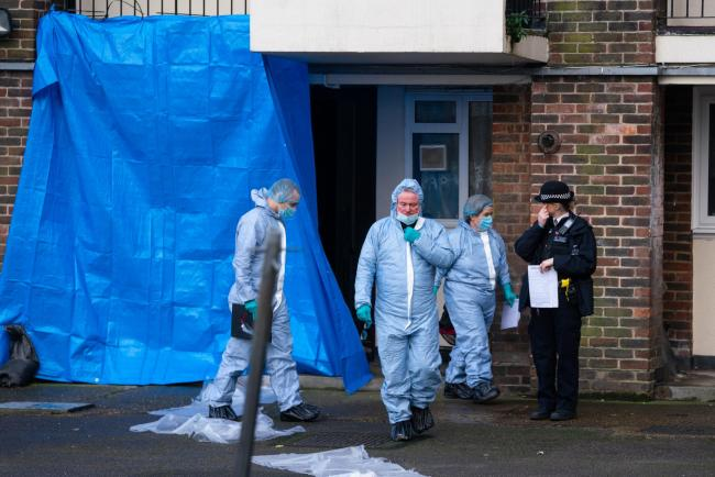 Police forensics officers at the scene of a fatal stabbing at flats on Wisbeach Road, in Croydon. Image: Dominic Lipinski/PA Wire .