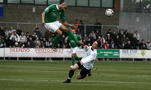 News Shopper: Lee Noble keeps his feet on the ground as a Lewes defender climbs high to win a header