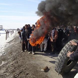 Afghans burn tyres during an anti-US demonstration over burning of Korans at a US military base, in Logar province, Afghanistan (AP)