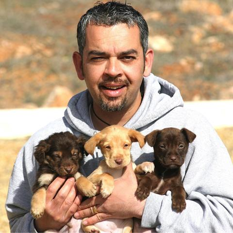 Peter with three rescue puppies who were found by a bin
