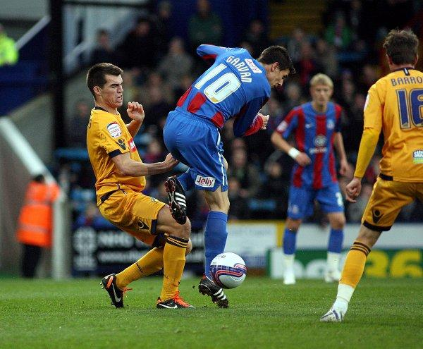 John Marquis (left) tackles Owen Garvan at Palace last year. EDMUND BOYDEN.