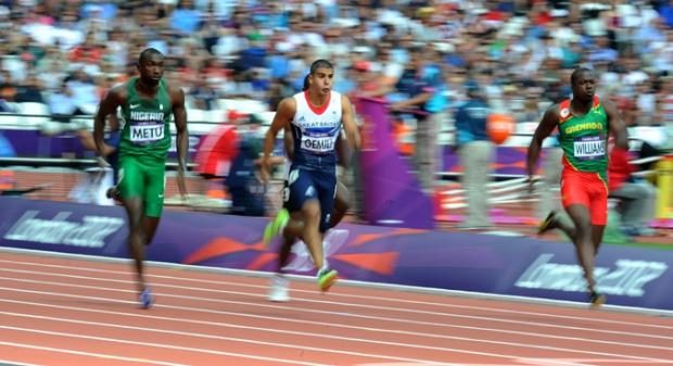 Adam Gemili competes with Nigeria's Obinna Metu (left) and Grenada's Paul Williams (right) in the Men's 100m heats (Picture: Owen Humphreys/PA Wire)