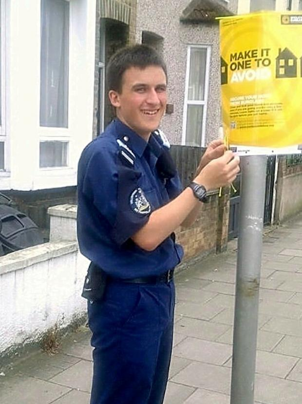 Cadet Alex Vale puts up a poster to spread the crime prevention message