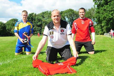 Kenny Wilkins lays Charlton Athletic Football Club shirt on pitch in memory of Carol Watson who died after battling cancer this year. Pictured with Edward Armstrong and Ben Murray
