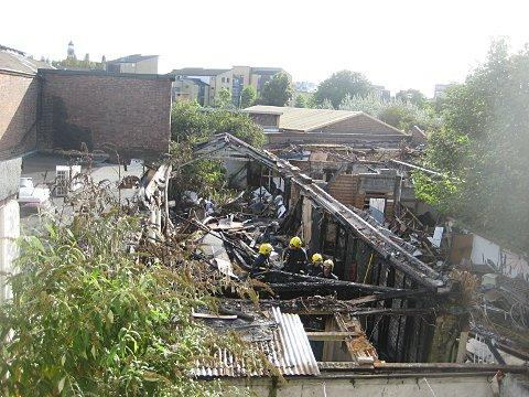 The charred remains of outbuildings behind shops and flats in New Cross Road