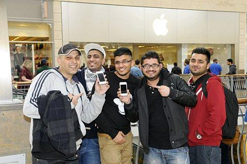 Excited customers show off their new phones at the Bluewater Apple store