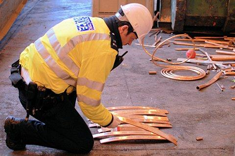 A metals task force officer examines the covered copper.