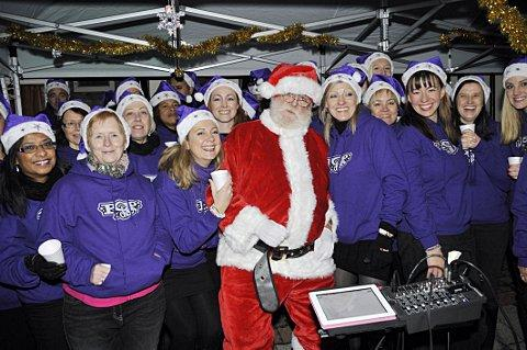 Singers and Santa Claus celebrate the lights being switched on