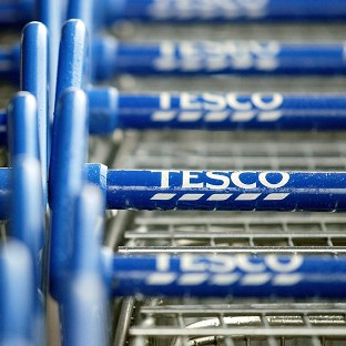 Tesco said its sales in the UK fell back into the red in its third quarter after a poor non-food performance held back improvements in its grocery arm