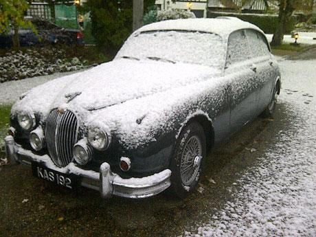 A classic Jaguar is covered in snow in Locksbottom
