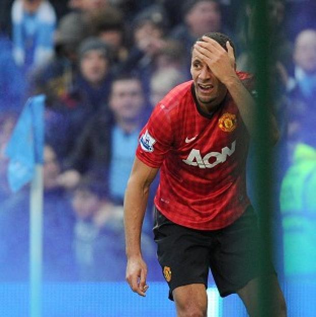 News Shopper: Manchester United's Rio Ferdinand holds his head after being hit by a coin at the Etihad Stadium