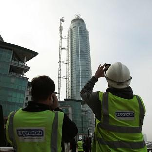 Construction workers take pictures of the damaged crane on top of St Georges Tower close to where a helicopter crashed in central London