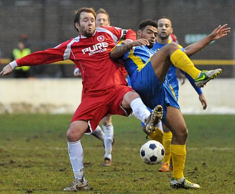 Wings captain Lee Clarke challenges for the ball with substitute Jordace Holder-Spooner