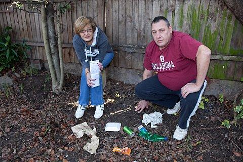 Graham Shepherd with his wife Lisbeth in their garden with some of the rubbish which has been thrown over their fence