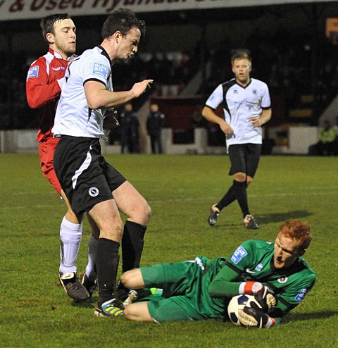 Visiting keeper Keeper James Russell collects the ball as Jake Gallagher is held off by a defender