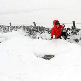 A six-year-old boy enjoys playing in the sno