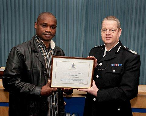 Stephen Izegbu receives his commendation from Met Police assistant commissioner Simon Byrne