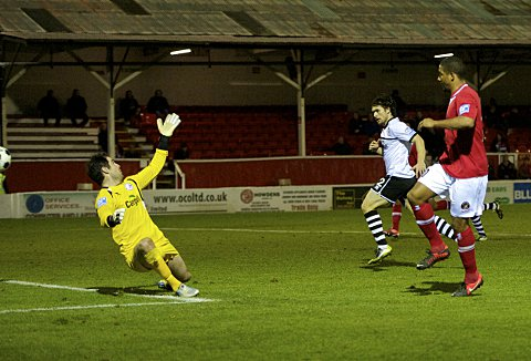 Scott chips the ball over visiting keeper James Bittner