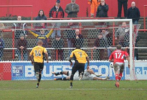 Preston Edwards gets down to save Andy Sandell's penalty