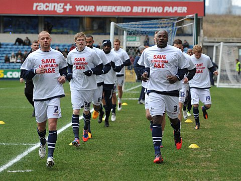 Millwall footballers warm up in Save Lewisham Hospital t-shirts at FA Cup quarter final