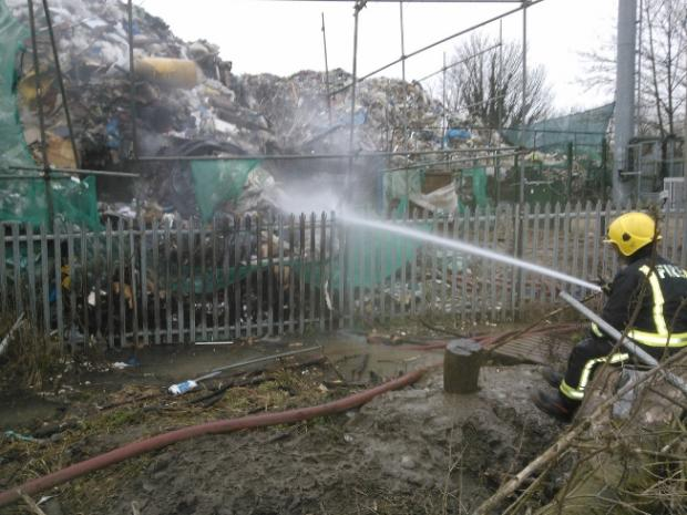 Firefighter tackles tonnes of smouldering waste at the recycling plant off Sevenoaks Way. Pics by Martin Peaple.