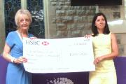 Barbara Ash, on the left, presents the cheque.