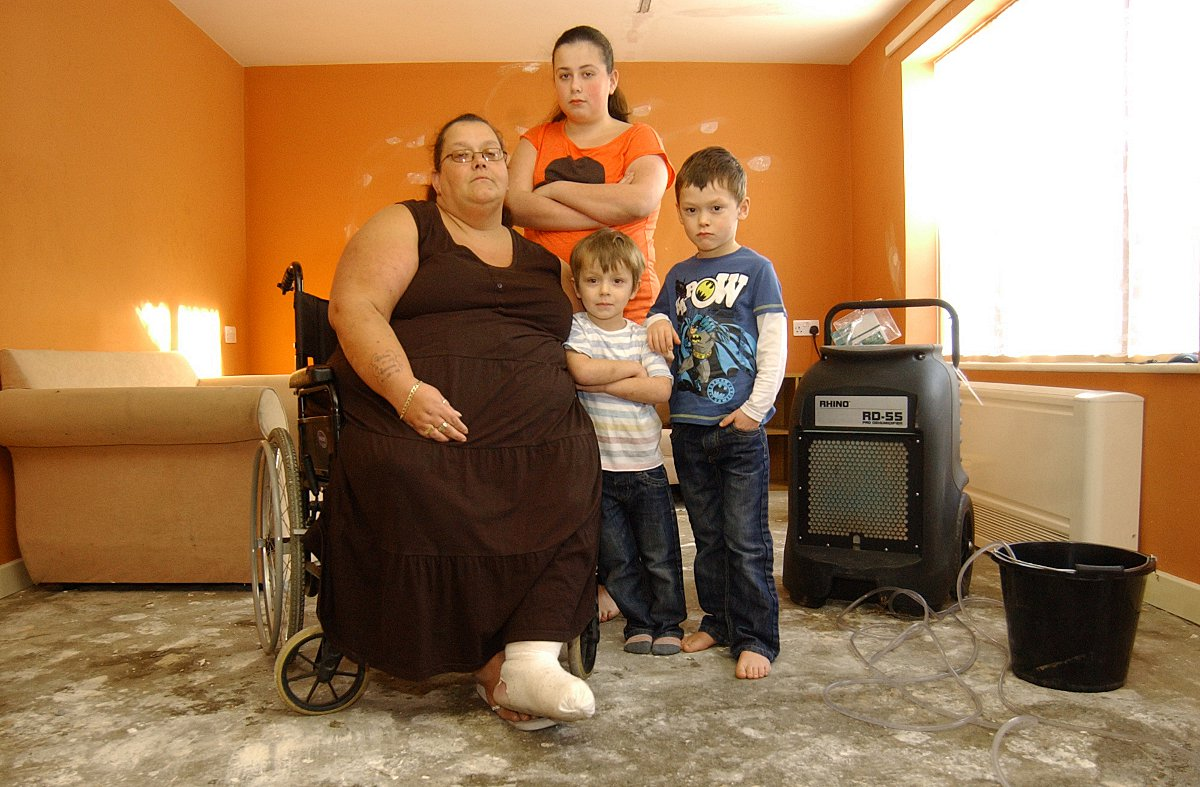 Tina Harman with her kids Chloe, 13, Callum, six, and Codi, four, in the front room.