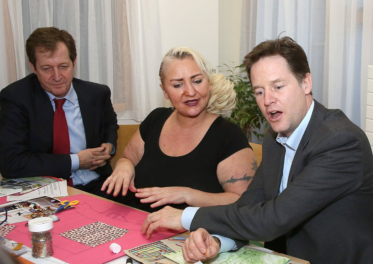 Patient Caroline Day tells Nick Clegg about the activity she is taking part in on Betts Ward as Alastair Campbell looks on.