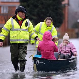 News Shopper: Volunteers help residents brave the flood water in Purley on Thames.