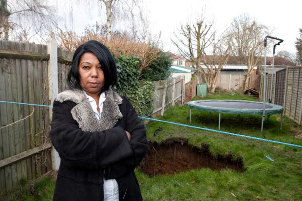 News Shopper: Gretel Davidson, 55, of Holmsdale Grove, thought her daughter Mia, 12, was exaggerating when she called her to say a huge black hole had appeared in the middle of their lawn.