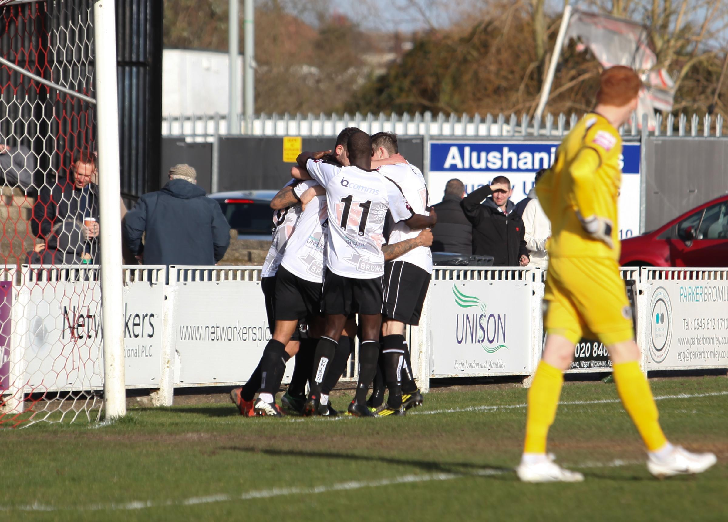 Boreham Wood's keeper looks on as Bromley players celebrate their second goal