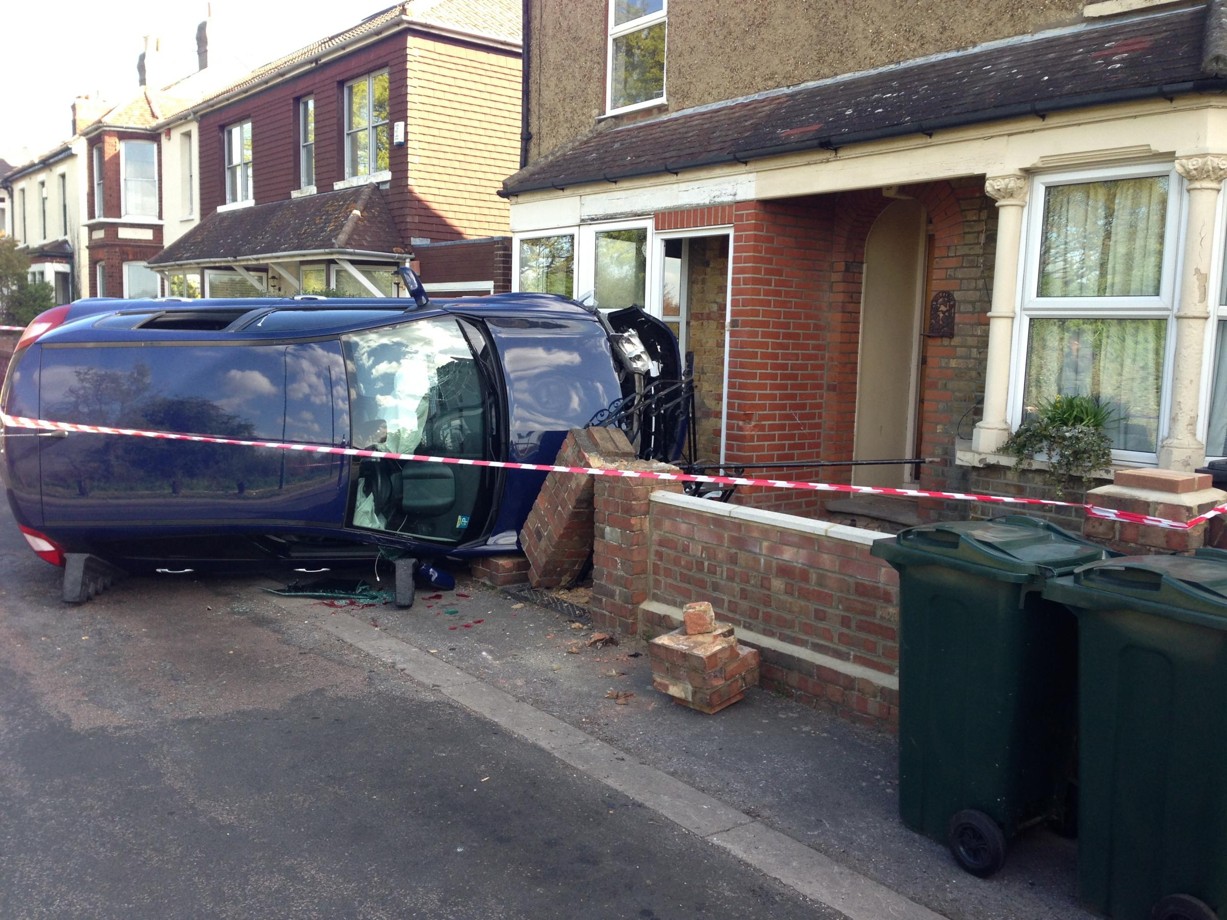 PICTURED: Lucky escape for Dartford mother after car flips and hits house