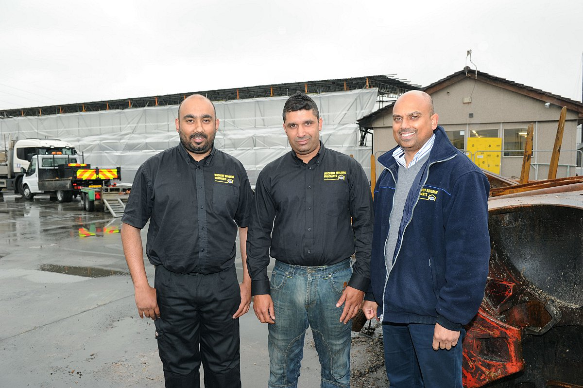 Left to right: Parm Guru, Jag Singh and Sanjeev Mall at the site of the fire with the new temporary warehouse in the background.