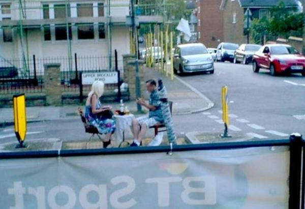 The couple, protected by bollards, enjoy a drink in the middle of the street