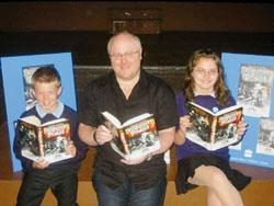 News Shopper: BOOKWORMS: Derek Landy enjoys his new book with Lewis Cochrane and Kirsty Harrison, aged 12.