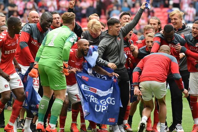 Josh Parker (centre), holding the blue flag with Albie Morgan, celebrating Charlton's promotion. Photo: Kyle Andrews Photography
